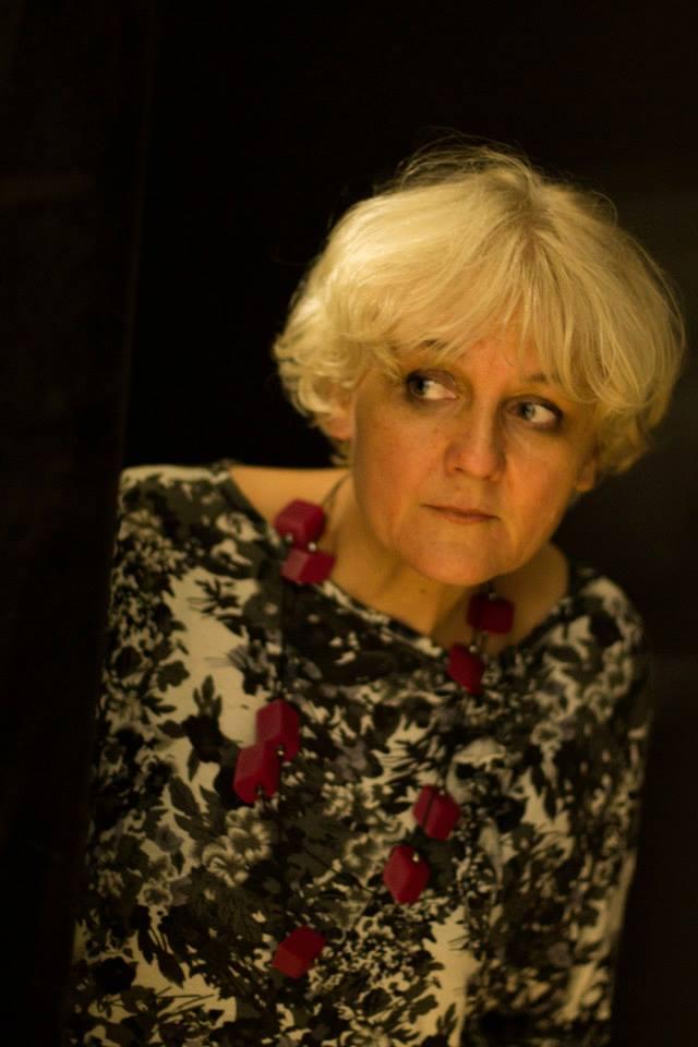 Kobieta ubrana w biało-czarną bluzkę, naszyjnik z wiśniowymi elementami. Posiada blond włosy.
