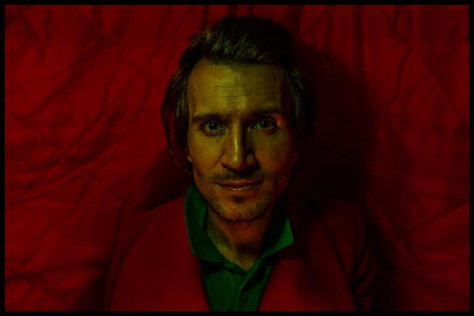 Mężczyzna na czerwonym tle. Ma na sobie czerwona marynarkę, wtapiającą się w tło. Mężczyzna ma lekki zarost. Na jego twarz pada żółte światło.