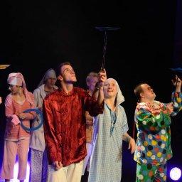 Grupa osób, w kolorowych strojach, stająca na scenie teatru, kręcąca talerzami cyrkowymi.