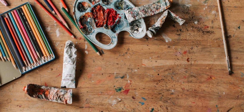 Stół, na nim farby, kredki, ołówki.